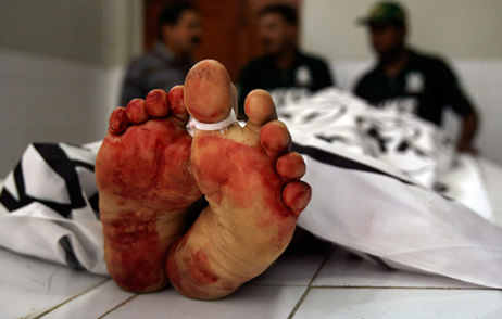 Policemen stand next to the body of a man who was killed by unidentified gunmen, at a morgue in Karachi's Abbasi hospital October 17, 2010