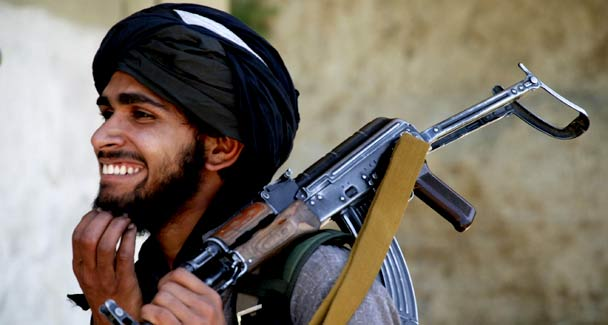 A Taliban militant smiles as he holds his weapon outside the mosque where tribal elders and Taliban met in Daggar