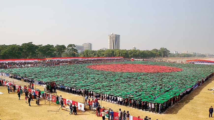 A staggering 27,117 people stand united, holding green and red boards above their heads, to put up the world's biggest ever human flag at the National Parade Ground on Victory day yesterday
