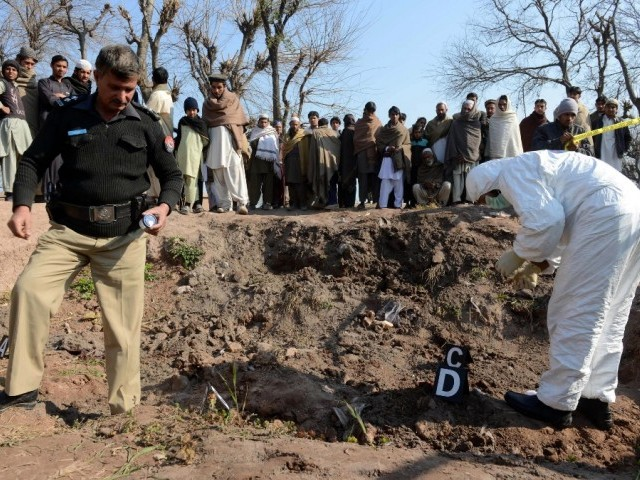 Security officials inspect the site of attack by militants in Peshawar on February 12, 2014