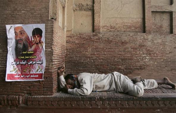 (A man takes a nap next to a poster of Osama bin Laden