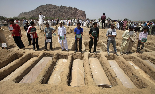 Members of the Ahmadi Muslim community hold the names of victims as they stood over their graves in Chenab Nagar, located in Punjab's Chiniot District